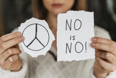 close-up-woman-holding-peace-sign-scaled